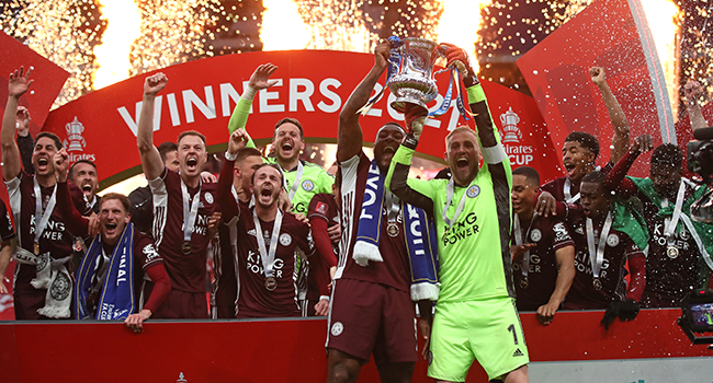 Leicester City's English-born Jamaican defender Wes Morgan (L) and Leicester City's Danish goalkeeper Kasper Schmeichel (R) hold up the winner's trophy as the Leicester players celebrate victory after the English FA Cup final football match between Chelsea and Leicester City at Wembley Stadium in north west London on May 15, 2021. Nick Potts / POOL / AFP