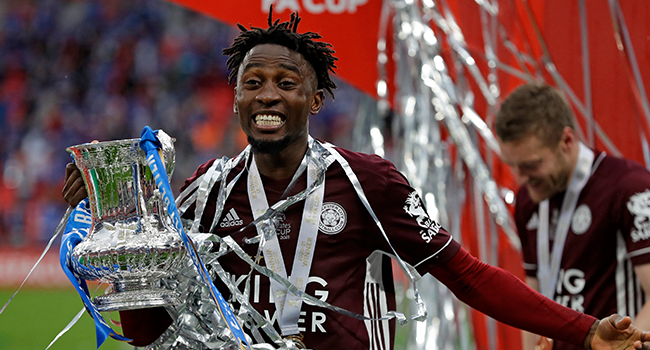 Leicester City's Nigerian midfielder Wilfred Ndidi holds the winner's trophy as the Leicester players celebrate victory after the English FA Cup final football match between Chelsea and Leicester City at Wembley Stadium in north west London on May 15, 2021. Kirsty Wigglesworth / POOL / AFP